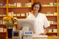 Pharmacist is registering the price of the medicine